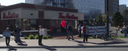Demonstrators outside Tim Horton's at the corner of Cedar and Paris Streets in Sudbury, Ontario, calling for an increase in the minimum wage to $14 an hour.
