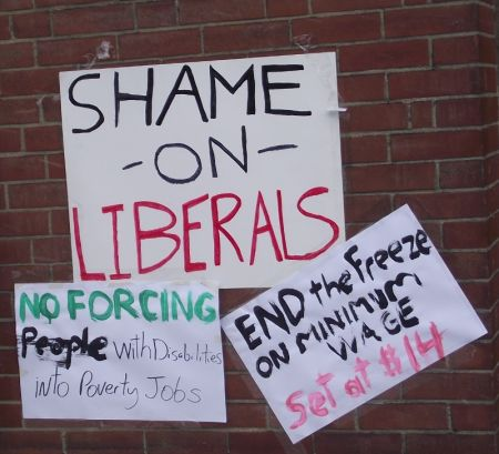Signs taped to the wall outside the office of Sudbury Liberal MPP Rick Bartolucci during the Solidarity Against Austerity action in Sudbury, Ontario on April 12, 2013. (Photo by Scott Neigh)