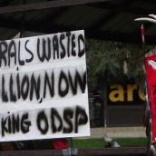 A sign at the Friday afternoon rally opposing potential attacks on disability benefits by the provincial Liberal government, next to the staff of the Indigenous Student Circle of Laurentian University. (Photo by Scott Neigh)