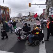 The Saturday march was lead by people with disabilities. This shows the march turning onto Elm Street from Elgin Street in downtown Sudbury. (Photo by Scott Neigh)