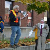 A dummy of Liberal MPP Rick Bartolucci looks on as one of the eleven people arrested last year at his office addresses the crowd. (Photo by Treana Campbell)